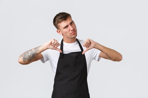 Dipendenti, negozi di alimentari e concetto di caffetteria. barista serio fresco e fiducioso, cameriere in grembiule nero che indica se stesso con espressione determinata, cura per gli ospiti, sfondo bianco