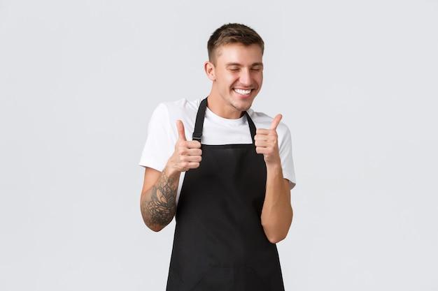 Dipendenti negozi di alimentari e caffetteria concetto felice barista carismatico in grembiule nero che ride un...