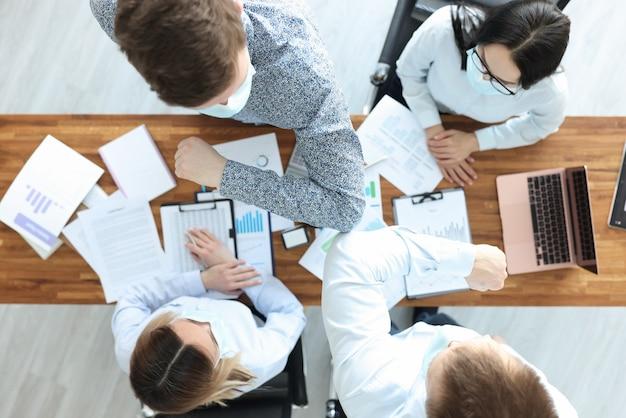 I dipendenti con maschere protettive mediche salutano i gomiti in ufficio. impatto del coronavirus