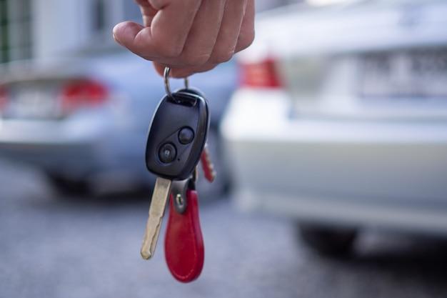 I dipendenti della vendita inviano le chiavi dell'auto ai turisti dopo aver stipulato un contratto di locazione. noleggia o acquista il concetto di auto