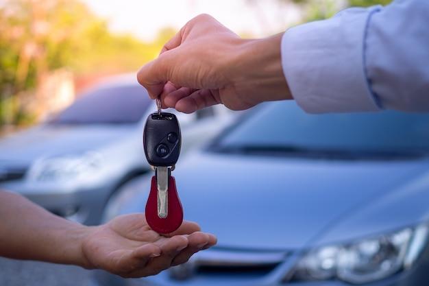 I dipendenti di vendita inviano le chiavi dell'auto ai turisti dopo aver stipulato un contratto di locazione. noleggia o acquista il concetto di auto
