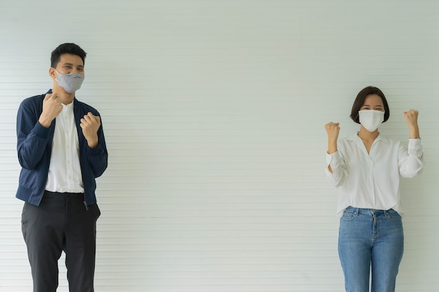 Dipendenti con maschera in piedi e mano alzata insieme allegra