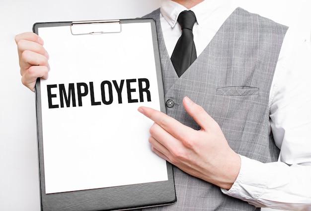 Iscrizione del datore di lavoro su un taccuino nelle mani di un uomo d'affari su uno sfondo grigio, un uomo indica con un dito il testo