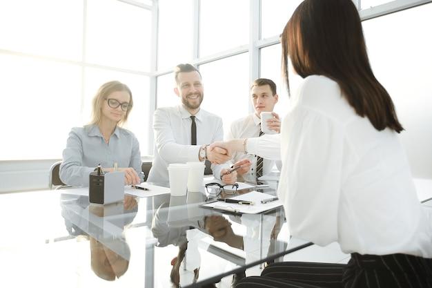 Il datore di lavoro stringe la mano al candidato per la posizione vacante. il concetto per il casting aziendale