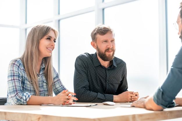 Il datore di lavoro parla ai dipendenti in una riunione in ufficio. concetto di affari