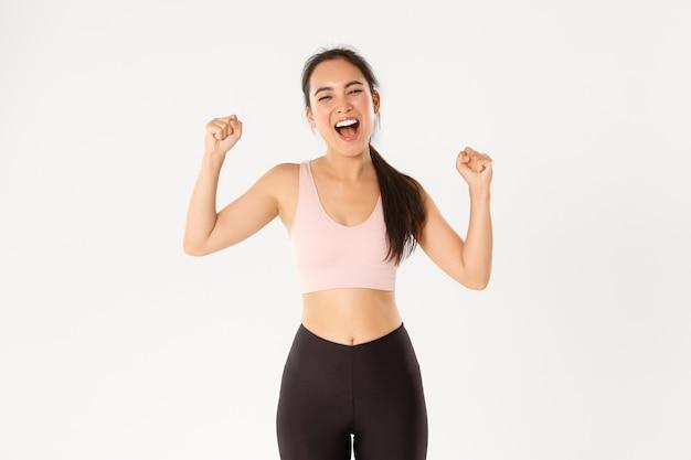 Atleta femminile asiatica potente e forte, ragazza fitness si incoraggia per un buon allenamento, pompa a pugno e grida di supporto, guadagnando l'obiettivo.