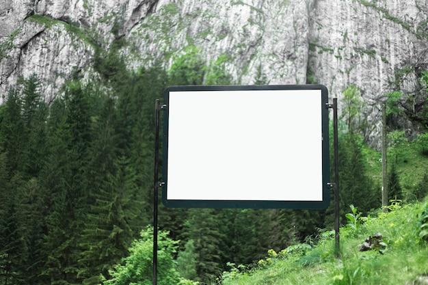 Cartellone pubblicitario vuoto nella foresta verde delle montagne.