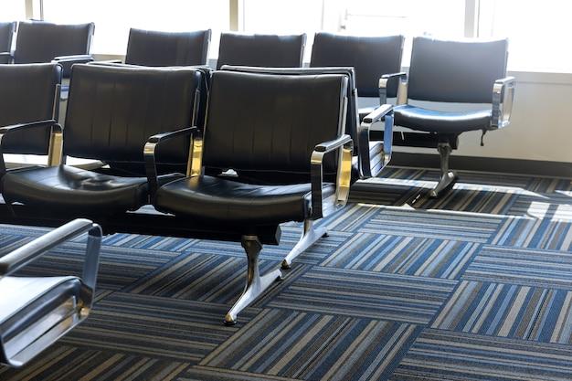 Area d'attesa vuota del terminal della sala partenze dell'aeroporto con sedie