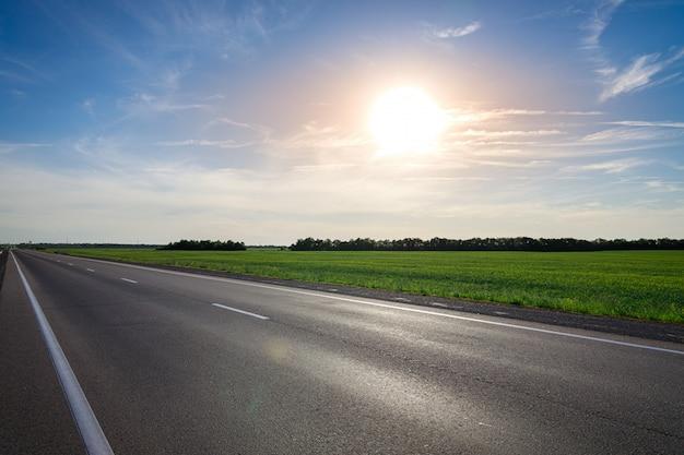 Strada principale vuota dell'asfalto contro il sole luminoso al tramonto