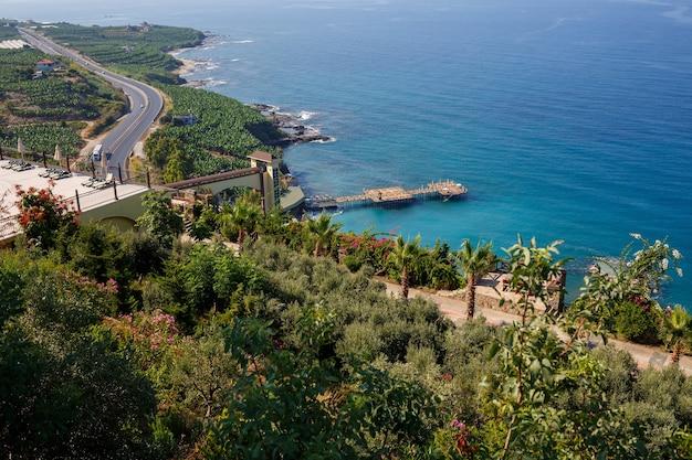 Una strada asfaltata vuota si snoda lungo la costa panoramica mozzafiato in una soleggiata giornata estiva. uno scatto spettacolare di una strada costiera che si affaccia sul cielo azzurro e sul calmo mar mediterraneo.