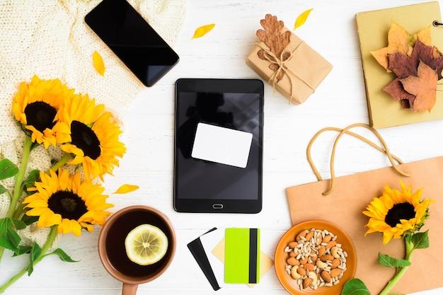 Carta di credito vuota su tablet con busta di foglie di girasoli regalo e tè con noci
