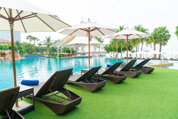 Sedia a sdraio vuota con ombrellone intorno alla piscina