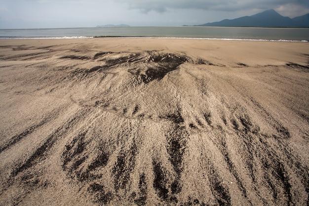Spiaggia vuota con diverso modello sulla sabbia