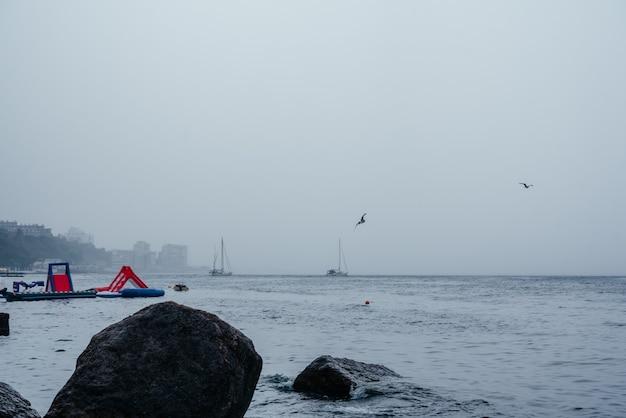 Una spiaggia deserta con scivolo gonfiabile galleggiante in un giorno di pioggia in autunno