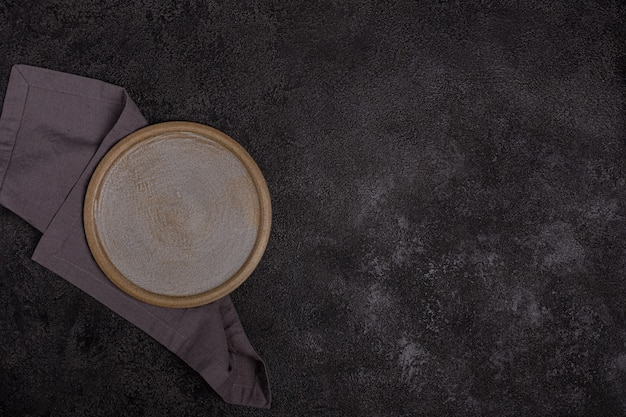 Un piatto di ceramica beige vuoto su uno sfondo nero scuro. tovagliolo di lino grigio. copyspace