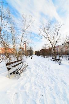 Una panchina vuota nel parco cittadino innevato. inverno.