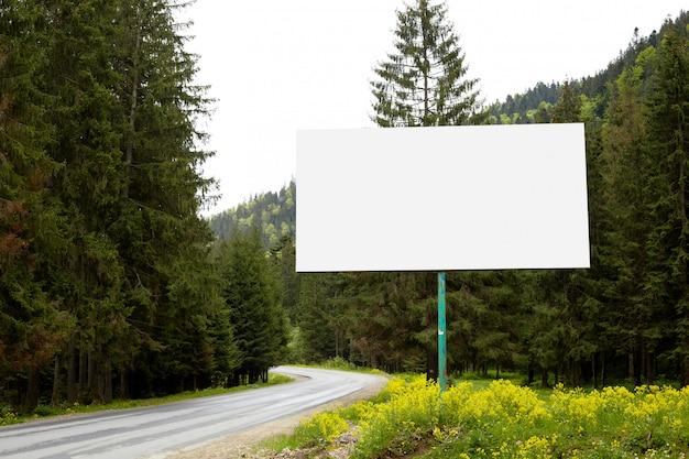 Tabellone per le affissioni vuoto o grande bordo dal lato della strada con la foresta e le colline verdi. pubblicità in bianco, mock up
