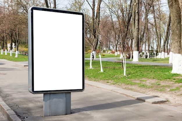Tabellone per le affissioni o lightbox vuoto sulla strada della città verde con sfondo bianco isolato