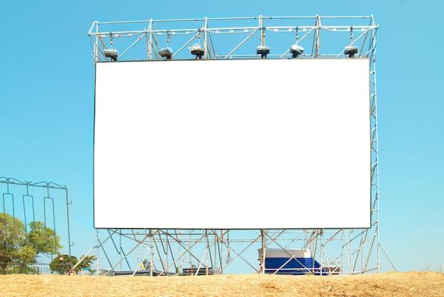 Tabellone per le affissioni vuoto con i precedenti del cielo blu