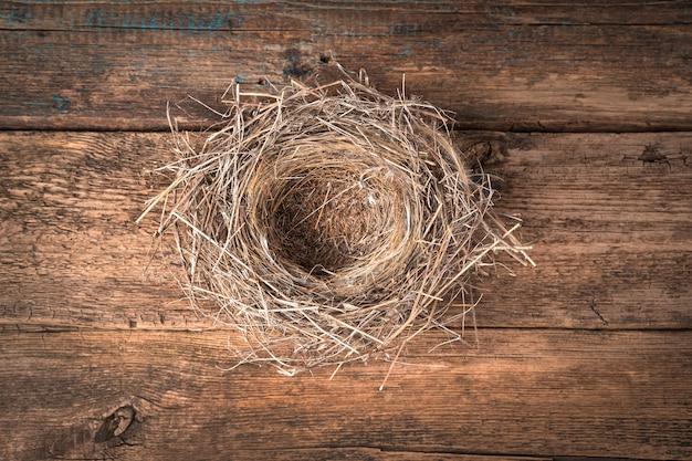 Un nido d'uccello vuoto fatto di erba secca su uno sfondo di legno. vista dall'alto con copia spazio. un concetto per il tuo design.