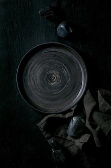Piatto in ceramica nero vuoto con pietre nere intorno sul tovagliolo in tessuto su fondo di legno nero. disposizione piana, spazio.