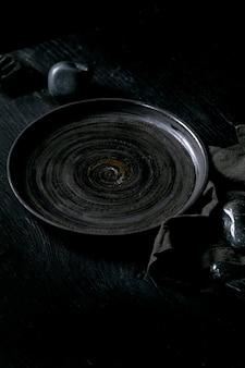 Piatto in ceramica nero vuoto con pietre nere intorno sul tovagliolo in tessuto su fondo di legno nero.