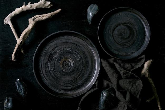 Piatti in ceramica neri vuoti con pietre nere e legno intorno su tovagliolo in tessuto su fondo di legno nero. disposizione piatta.