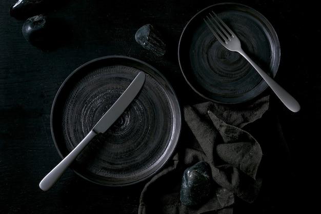 Piatti vuoti in ceramica nera con posate e pietre nere intorno su tovagliolo in tessuto su fondo di legno nero. disposizione piana, spazio.
