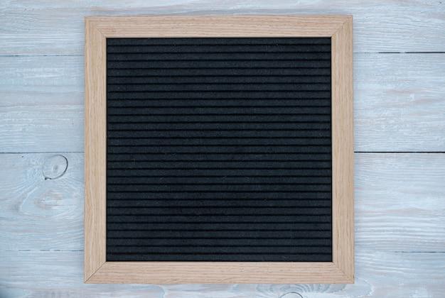 Lavagna vuota in feltro nero su fondo di legno naturale