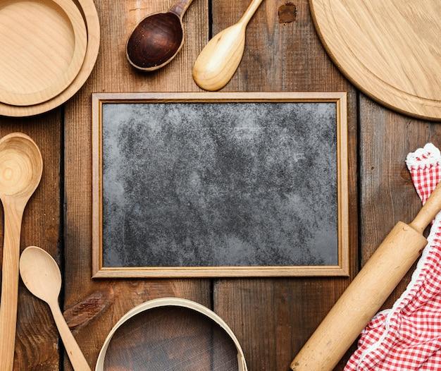 Cornice nera vuota e oggetti vintage da cucina in legno: setaccio, mattarello, cucchiai vuoti e piatti rotondi sulla tavola di legno marrone, vista dall'alto