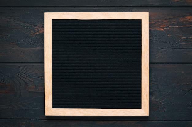 Letterboard nero vuoto su fondo di legno scuro. modello di progettazione.