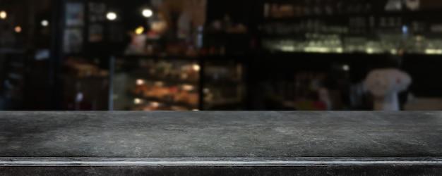 Piano d'appoggio di pietra di marmo nero vuoto e fondo vago dell'interno della caffetteria, del caffè e del ristorante