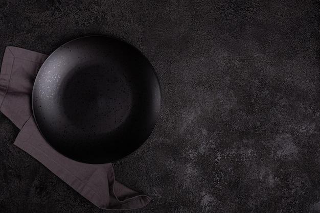 Un piatto di ceramica nero opaco vuoto su uno sfondo nero scuro. un tovagliolo di lino grigio.
