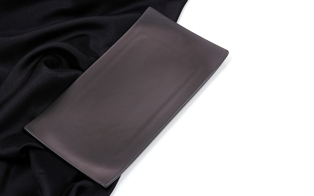 Svuoti il piatto ceramico moderno di rettangolo nero con struttura di seta della tovaglia