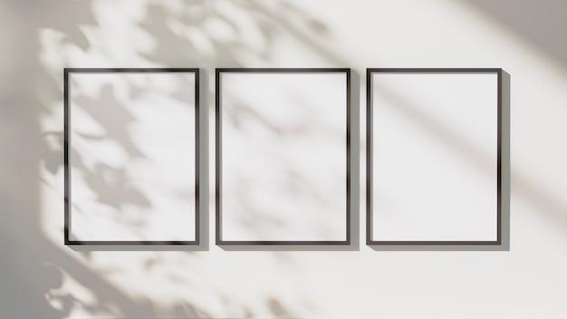I telai rettangolari verticali neri vuoti deridono con le ombre delle foglie e la luce solare sul fondo bianco della parete, rappresentazione 3d