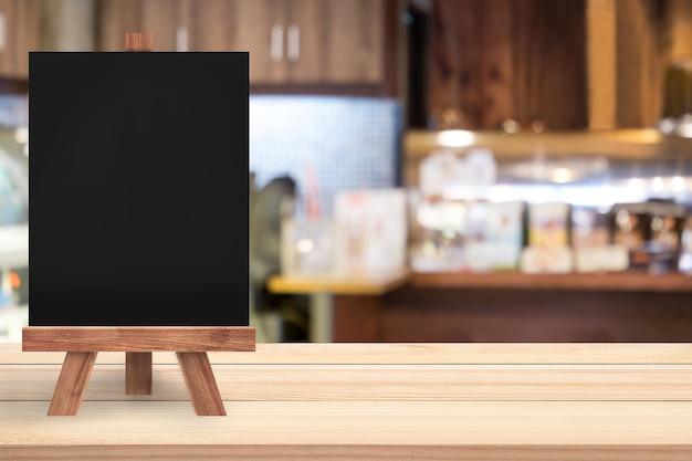 Una lavagna vuota con cavalletto è su un tavolo di legno in un ristorante / bar