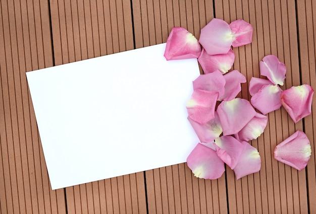Svuoti la carta in bianco con il petalo di rosa su di legno.