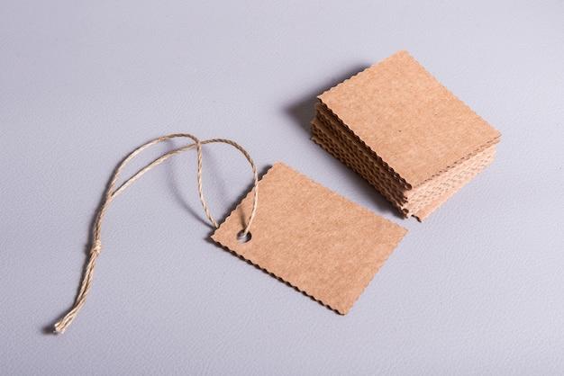 Etichette in bianco vuote dell'etichetta del cartone con il foro e la corda