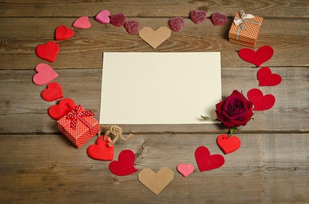 Vuoto vuoto per il testo intorno a molti cuori fatti a mano e due scatole regalo a forma di cuore sulla superficie della tavola di legno