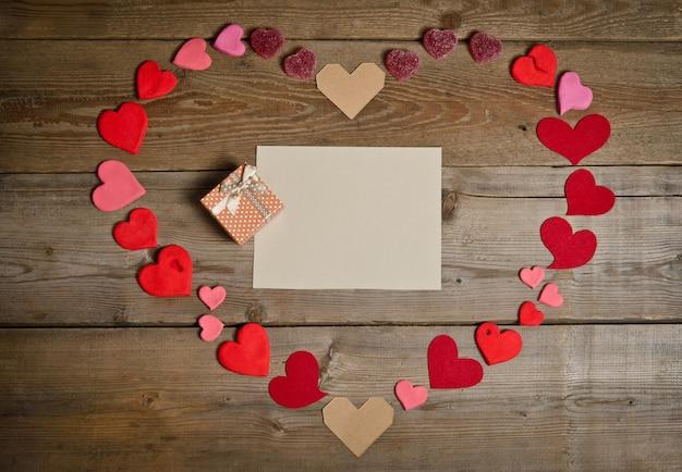 Vuoto vuoto per il testo con confezione regalo intorno a molti cuori fatti a mano a forma di cuore sulla superficie della tavola di legno