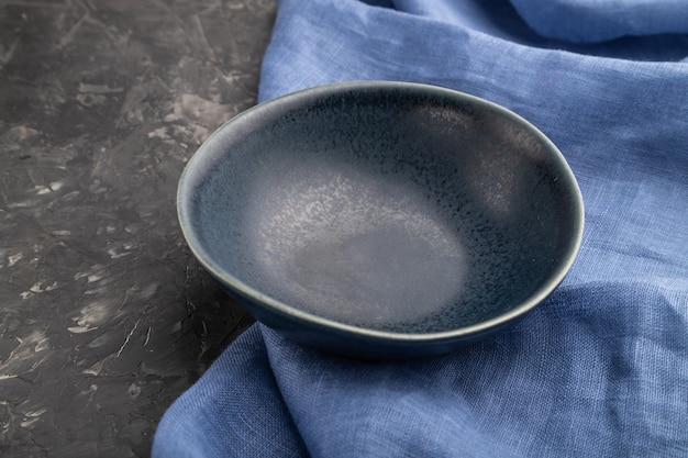 Ciotola in ceramica blu vuota su sfondo di cemento nero e tessuto di lino blu