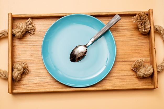 Piatto blu vuoto con cucchiaio su vassoio in legno