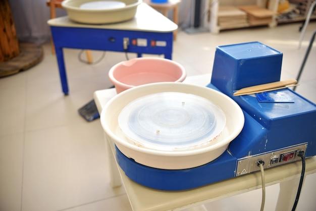 Un tornio da vasaio blu vuoto viene preparato per la pratica di gruppo della ceramica lepui dall'argilla. strumenti per realizzare prodotti di argilla in un laboratorio di ceramica da un maestro.