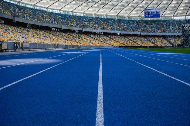 Pista da corsa blu vuota allo stadio olimpico sullo sfondo di tribune vuote