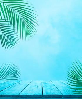Vuoto del piano del tavolo in legno blu con foglia di cocco su sfondo cielo morbido.per la visualizzazione del prodotto di montaggio o il layout keyvisual di design.vacanze estive