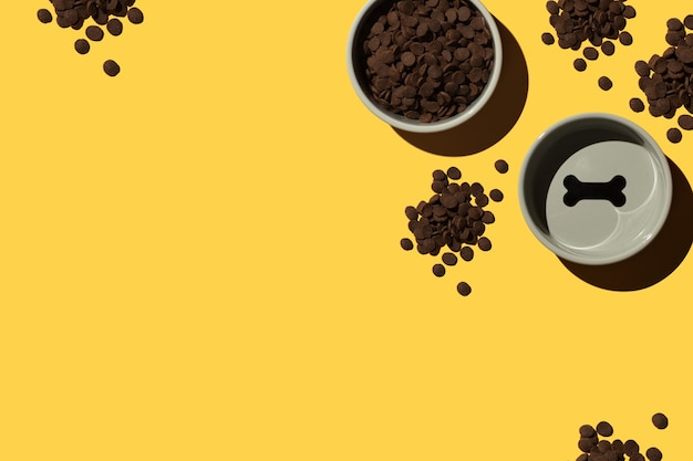 Ciotola vuota e ciotola con cibo per cani secco su sfondo giallo
