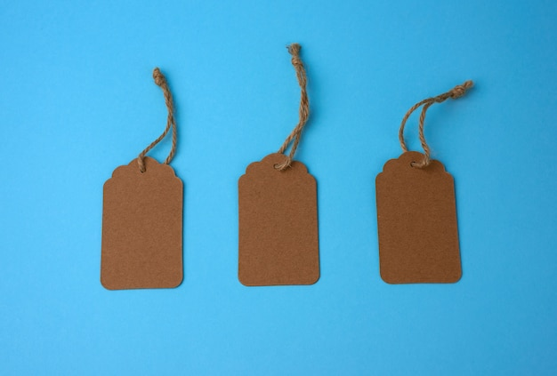 Etichette vuote della carta marrone legate con corda bianca. cartellino del prezzo, etichetta regalo, etichetta di vendita