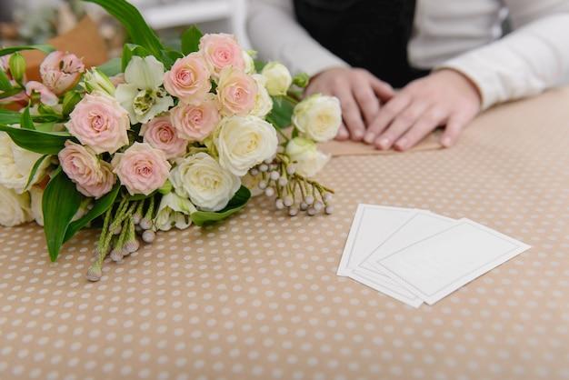 Biglietti da visita vuoti sul tavolo con rose bianche e rosa accanto al fioraio