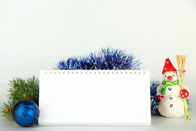 Calendario vuoto, decorazioni di capodanno e abete su sfondo chiaro