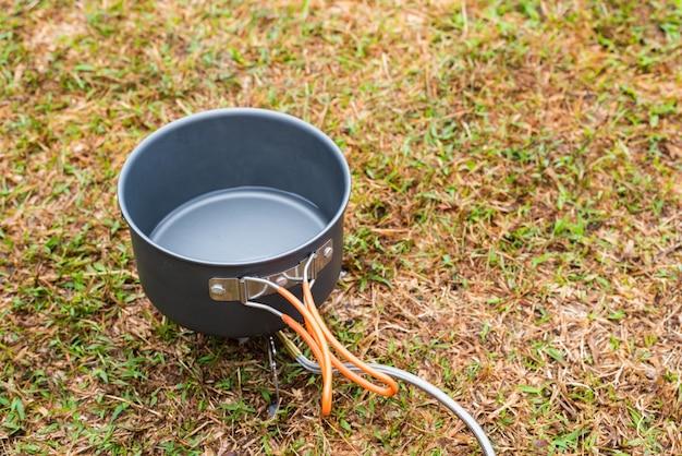 Lattina vuota o padella sul fornello da campeggio portatile sull'erba.